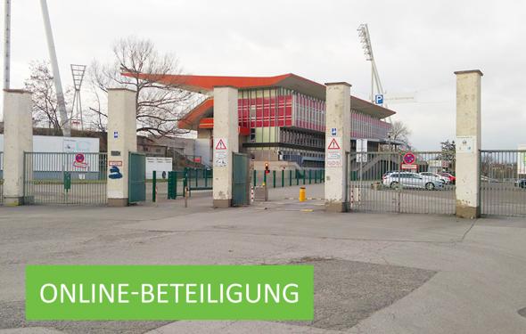 Eingang des Friedrich-Ludwig-Jahn-Sportparks mit dem Großen Stadion im Hintergrund