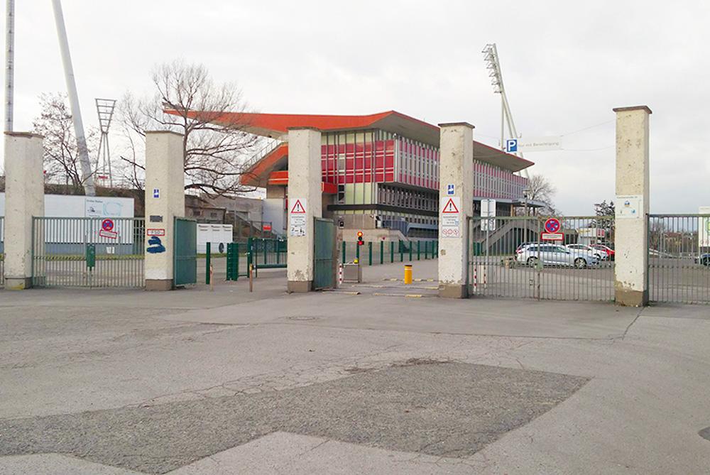 Einganssituation de Jahnsportparks. Vier drei Meter hohe Betonsäulen, dazwischen offene und geschlossene Zäune. Im Hintergrund das Große Stadion. Winterwetter mit grauem Himmel.